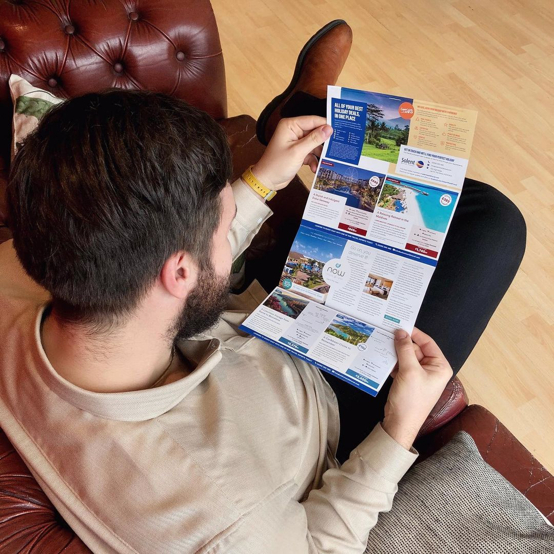 Man sitting down holding a holiday brochure designed by 6rs