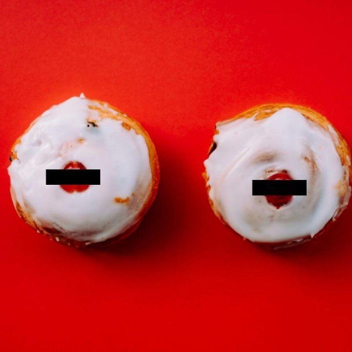 Bold image looking down on two iced buns with a cherry on top on a red background